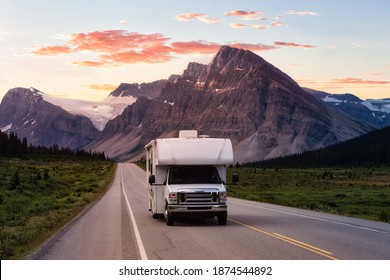 Scenic road in the Canadian Rockies during a vibrant sunny summer sunrise. White RV Driving on route. Taken in Icefields Parkway, Banff National Park, Alberta, Canada.