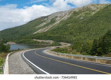 Scenic Road in Newfoundland:  A two-lane highway curves past an ocean inlet and climbs into a mountainous area in Gros Morne National Park on the west coast of Newfoundland.