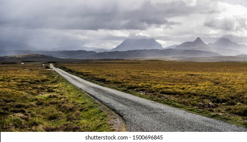 Scenic road  in northern Scotland with a loch visible far away
