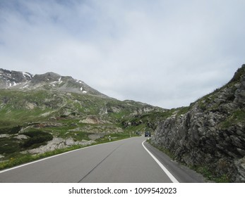 Scenic road and surrounding Alpine environment leading up to San Bernardino Pass on a cloudy Summer day in Canton Grisons - Switzerland