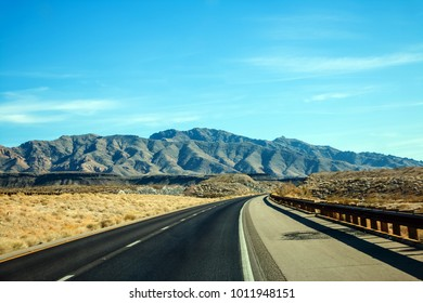 Scenic road travel in the desert with mountains and road signs