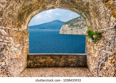Scenic rock arch balcony overlooking the iconic volcano Vesuvius from Sorrento in the Bay of Naples, Italy