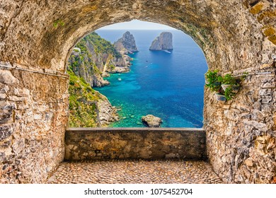 Scenic rock arch balcony overlooking the beautiful Faraglioni rocks, island of Capri, Italy