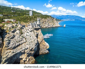 Scenic rocky coastline with castle Swallow's Nest at the precipice in Crimea, Russia. Swallow's Nest is a famous landmark of Crimea. Aerial beautiful view of the Black Sea coast of Crimea in summer.