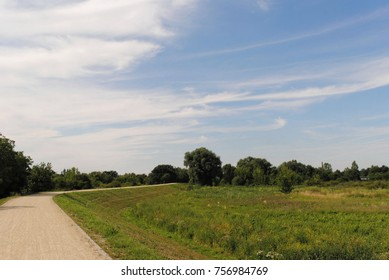 Scenic rural landscape of levees and moisty meadow and bike path. Beautiful sky with clouds. Trees and bushes. Nature view.
