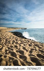 scenic sandy beach on atlantic coastline with breaking waves in blue sky, capbreton, les landes, france