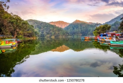 Scenic Sattal lake at Nainital with tourist paddle boats at sunset with picturesque landscape view at Uttarakhand India.