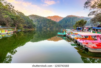 Scenic Sattal lake with tourist paddle boats at sunset with picturesque landscape view at Nainital Uttarakhand India.
