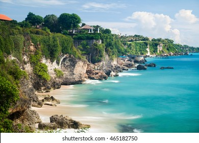 Scenic sea landscape, Bali. High cliff on tropical Pantai beach in Bali, Indonesia. Tropical nature of Bali, Indonesia. Beautiful blue sea water, white sand beach and green tropics of Bali shoreline