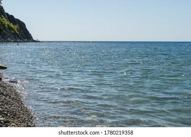 Scenic sea landscape with blue water of Black Sea with rocky coast on the horizon. Olginka village, Tuapse, the Black Sea, Russia.