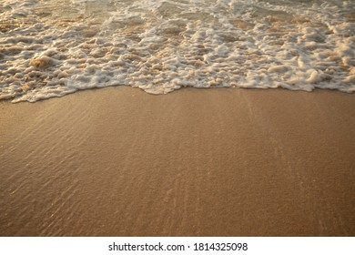 Scenic seascape. Milky foam waves at sandy beach. Sunset time. Waterscape for background. Selected soft art focus. Sunlight reflection on the water and wet sand. Copy space. Balangan beach, Bali