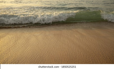 Scenic seascape. Milky foam waves at sandy beach. Sunset. Waterscape for background. Selected soft art focus. Sunlight reflection on the water. Wet sand. Balangan beach, Bali, Indonesia