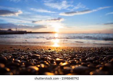 Scenic seaside morning view with clouds and focus on a stones. Shallow depth of field and beautiful bokeh.