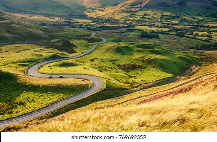 Scenic serpentine road in warm sunset light at summer. Elevated view from grassy slopes of Mam Tor