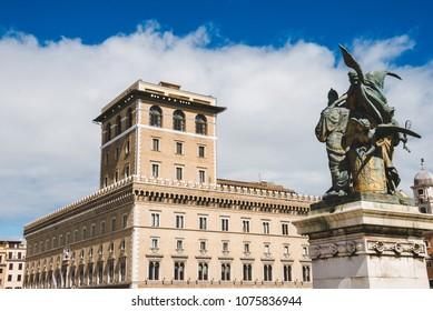 scenic shot of beautiful Palazzo Venezia from Piazza Venezia (Venezia Square) with bronze statue on foreground, Rome, Italy