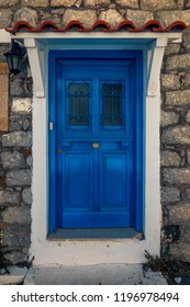 Scenic shot of a picturesque door entrance into a stone house  painted in the greek colours blue and white on Samothrace Island in the city of Samothraki