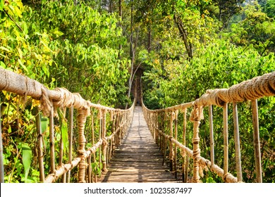 Scenic simple suspension bridge over gorge. Beautiful footbridge made from rope and bamboo. Amazing hanging bridge among green woods.