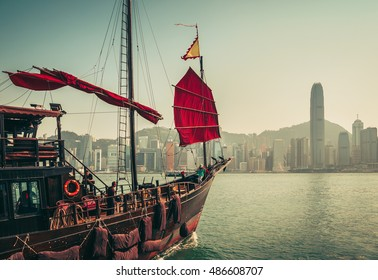 Scenic skyline of a big city with skyscrapers and old traditional boat. Victoria harbor. Famous landmark of Hong Kong. Vintage effect.