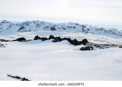 Scenic snow covered land and mountains in Iceland during winter.