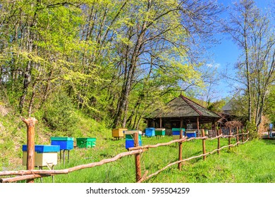 Scenic spring blue sky landscape of rustic apiary with wooden beehives behind the fence on sunny day. Quiet authentic peasant's life at Russian Caucasus mountain countryside.