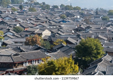 Scenic street in the Old Town of Lijiang, Yunnan province, China. Wooden facades of traditional Chinese houses. The Old Town of Lijiang is a popular tourist destination of Asia.