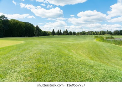 Scenic summer landscape with green lawns in a park and curving embankments under a sunny blue sky with clouds