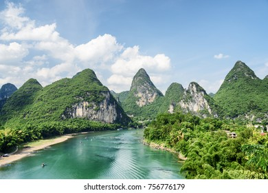 Scenic summer sunny landscape at Yangshuo County of Guilin, China. View of beautiful karst mountains and the Li River (Lijiang River) with azure water. Amazing green hills on blue sky background.