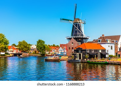 Scenic summer view of the Old Town architecture, mill and canal embankment in Haarlem, Netherlands