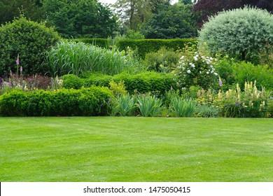 Panoramasicht auf den schönen Landschaftsgarten im englischen Stil mit grünem Rasenmäher, grünen Bäumen und farbenfrohen Blumenbeeten