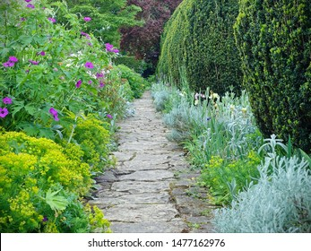 Scenic Summertime View of a Stone Paved Path through a Beautiful English Style Landscape Garden Lined by Flowers in Bloom