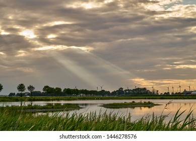"""scenic sunrays come out of a cloudy sunset sky behind a pond of the biotope """"Kleipütte"""" in Brake (Unterweser), district Wesermarsch, Germany"""