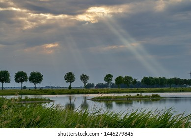 """scenic sunrays come out of a dark cloudy sunset sky behind a pond of the biotope """"Kleipütte"""" in Brake (Unterweser), district Wesermarsch, Germany"""