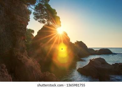 Scenic sunrise on sea coast in Spain, Costa Brava. Morning sea landscape in Lloret de Mar. Sun shines behind rock in mediterranean bay