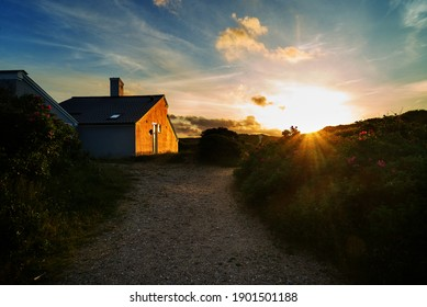 scenic sunset behind the dunes of Vejers Strand (Denmark - the golden light shines on the facade of a simple contemporary vacation house