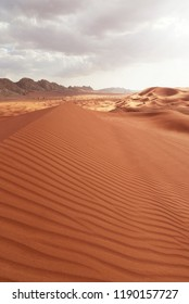 Scenic sunset landscape view of the red desert of Dubai near the rock mountain of Sharjah in the United Arab Emirates
