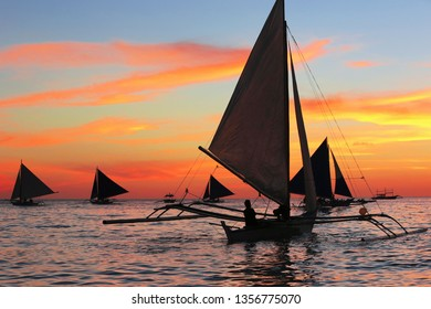 Scenic sunset over Boracay coast with sailboats, Philippines