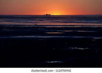 scenic sunset over the mud flat in Cuxhaven, Germany, a silhouette of a ship can be seen far away at the flickering horizon