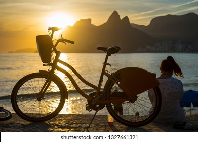 Scenic sunset view of Ipanema Beach with Two Brothers Mountain towering above the silhouette of a woman with a bicycle sitting at the Arpoador overlook in Rio de Janeiro, Brazil