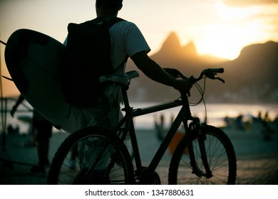 Scenic sunset view of Ipanema Beach from Arpoador with silhouette of a surfer with a bicycle in front of Two Brothers mountain in Rio de Janeiro, Brazil