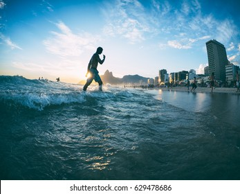 Scenic sunset view of Ipanema Beach with waves crashing on the shore in Rio de Janeiro, Brazil