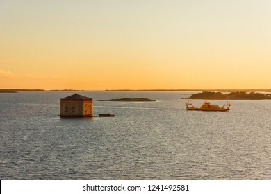 Scenic sunset view on Godnatt naval keep (fortress in the sea for defense of naval harbor) and vessel in the Baltic Sea near Karlskrona, Sweden. Part of the UNESCO World Heritage Site Karlskrona.