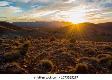 Scenic sunset view with sunburst from over the mountain ranges at Hucks Lookout within the Ikara Flinders Ranges National Park, South Australia. Looking toward Wilpena Pound.