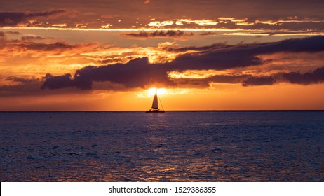 Scenic sunset viewed from Lahaina harbor, Maui, Hawaii. A silhouette of sail boat against setting sun