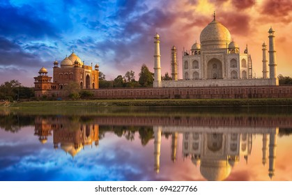 Scenic Taj Mahal at sunset with moody sky and water reflections.