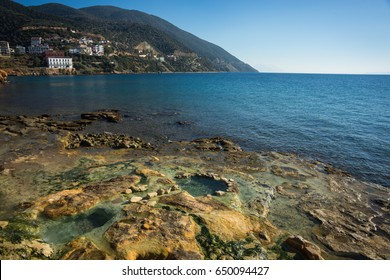 Scenic thermal springs and rock formations on the beach in Loutro Edipsou, Evia, Greece