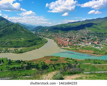 Scenic top view to old georgian  small town located at valley of confluence two mountain rivers with different colors of water. Mtskheta,Georgia.