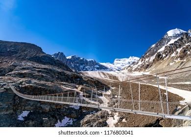 Scenic veiw of hanging bridge over the Glacier de Corbassiere on a mountain trail around Valais Swiss Alps.