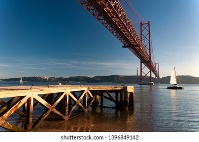 Scenic view of the 25 of April Bridge (Ponte 25 de Abril) over the Tagus River with sailing boats, in the city of Lisbon, Portugal