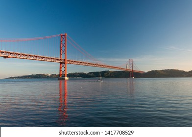 Scenic view of the 25 of April Bridge (Ponte 25 de Abril) over the Tagus River in the city of Lisbon, Portugal; Concept for travel in Portugal