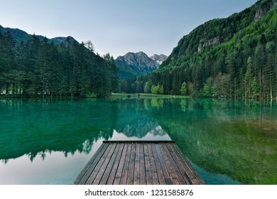 A scenic view of the alps taken early in the morning at Jezersko lake, Slovenia. Scenic background and nice water reflection with wooden pier in the foreground.